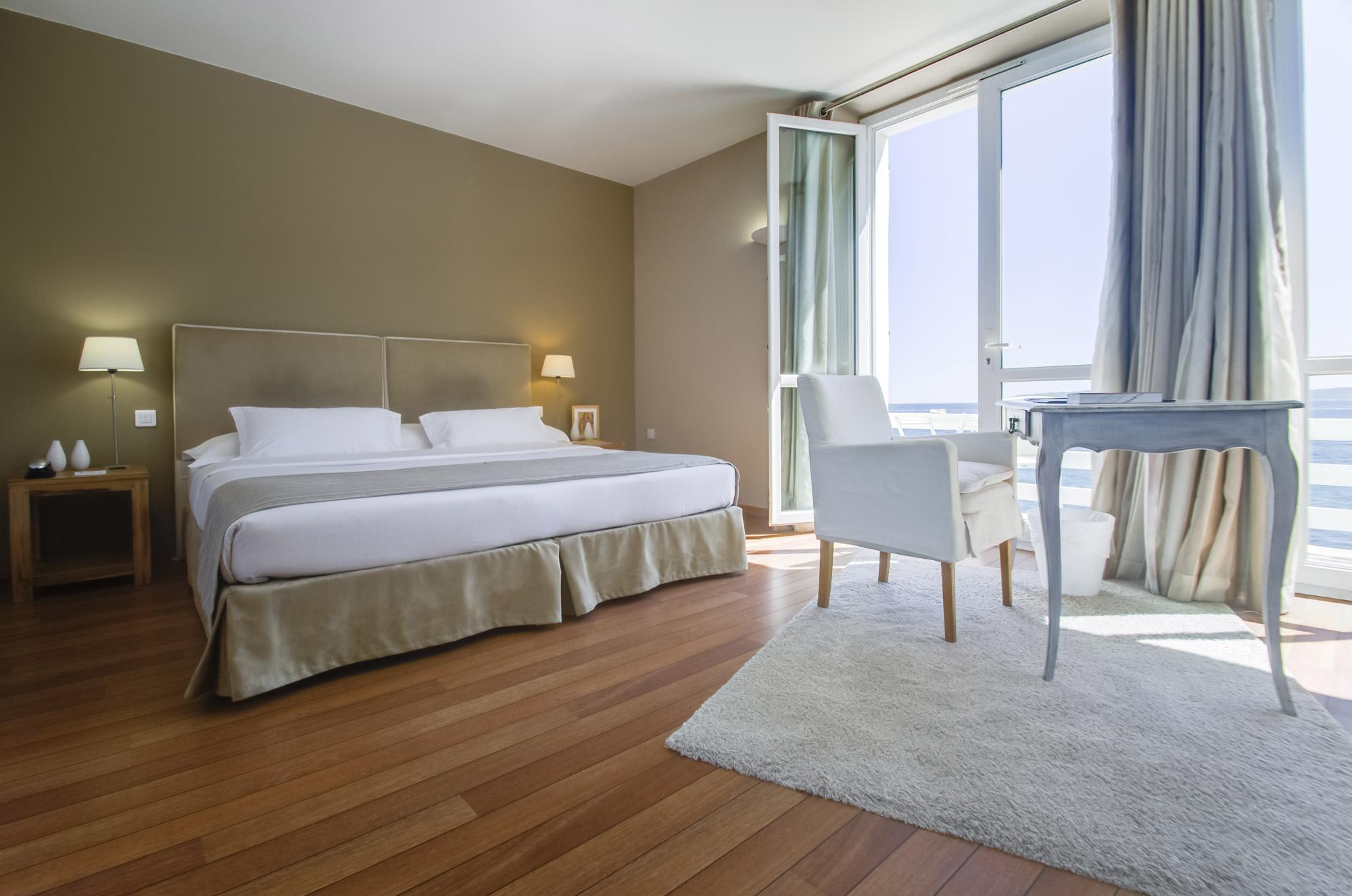 Chambre avec parquet en bois et grande baie vitrée baignée de soleil, donnant sur la mer