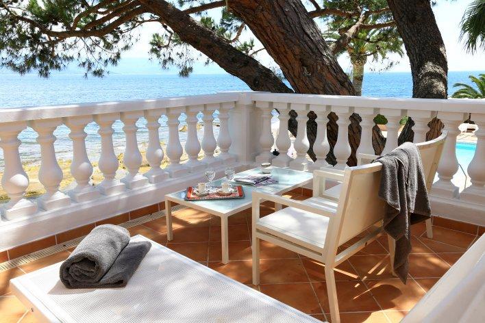Balcon à colonnes traditionnelles avec vue sur mer, sur lequel sont installées une table basse et deux fauteuils