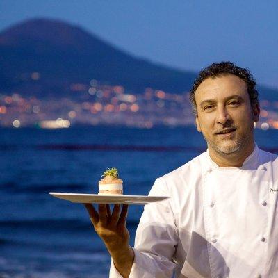 Portrait de chef devant un paysage de mer et de montagne, présentant une entrée dressée sur une assiette