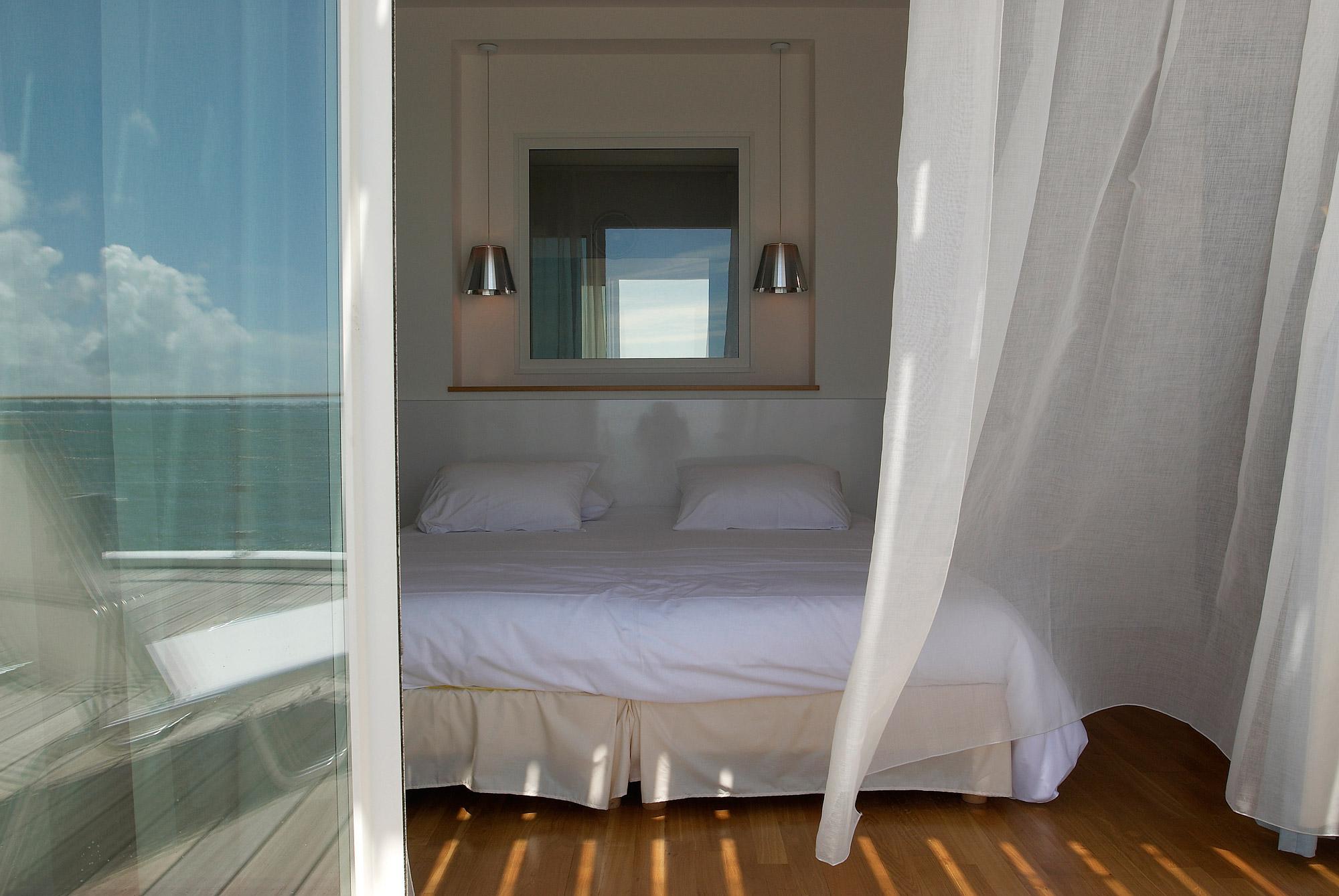 Chambre spacieuse avec le vent soufflant dans les voilages et le reflet de l'eau dans la baie vitrée