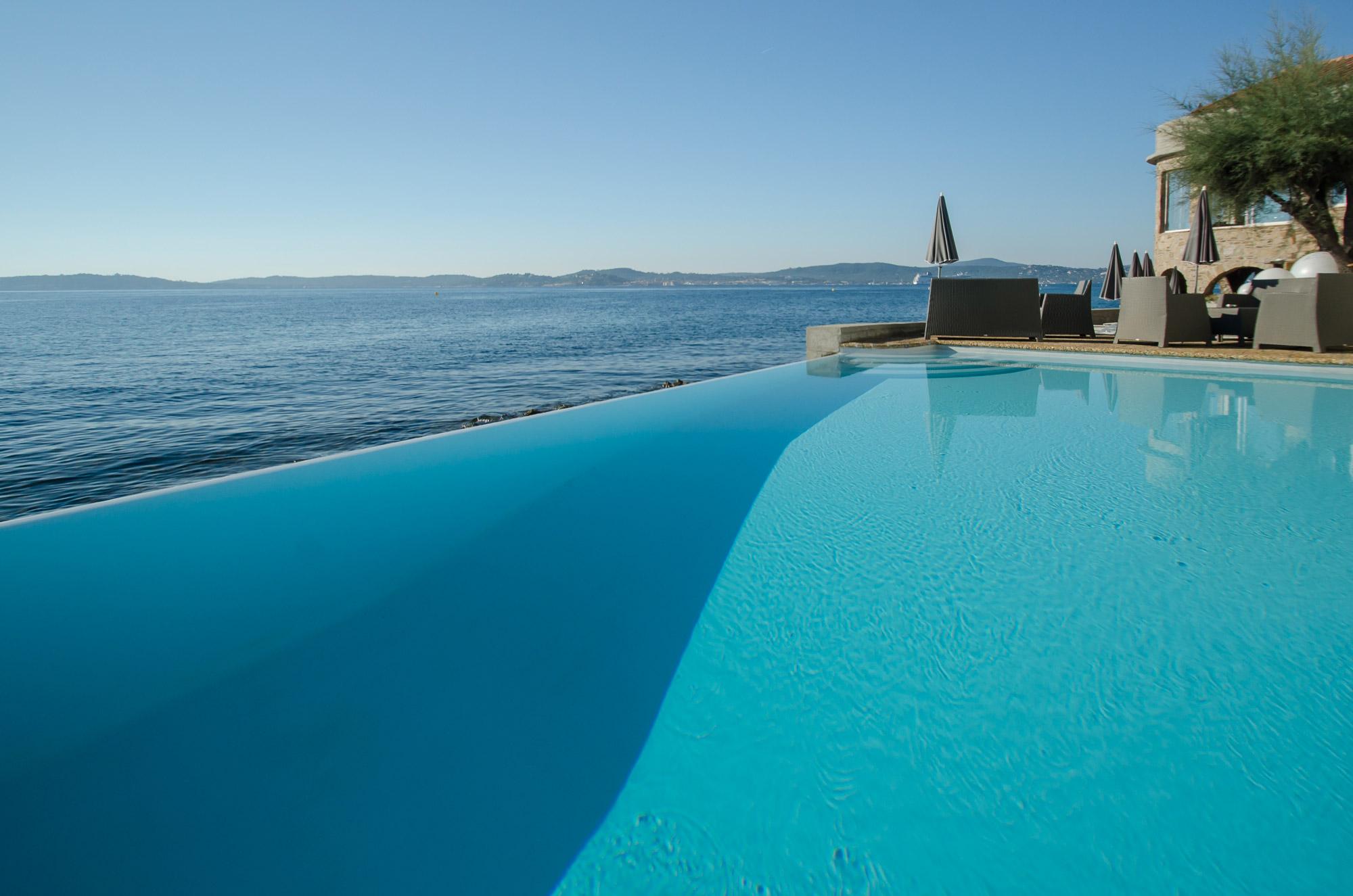 Piscine à débordement avec vue sur la mer Méditerranée, en arrière-plan une terrasse pour prendre un bain de soleil