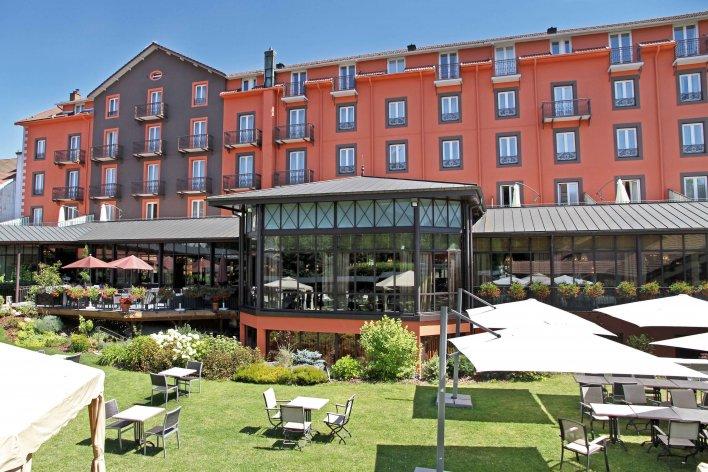 Façade rouge et noire du Grand Hôtel & Spa de Gérardmer, devant la verrière ouverte sur le jardin de l'établissement