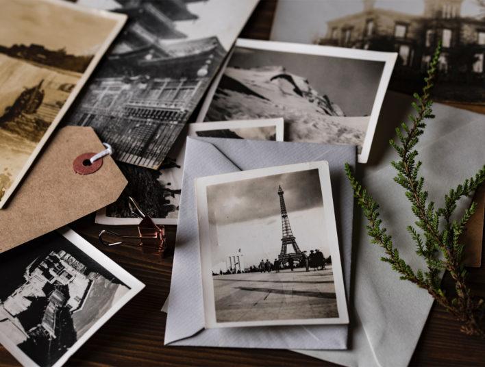 Table en bois parsemée de photos en noir et blanc dont la Tour Eiffel à Paris