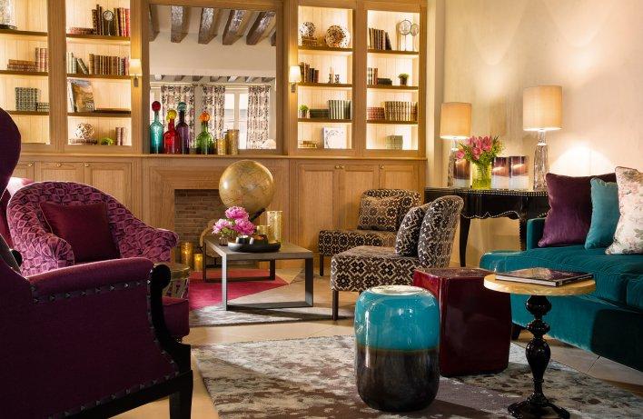 Salon avec bibliothèque en bois, cheminée, fauteuils colorés en velours dans une ambiance chic