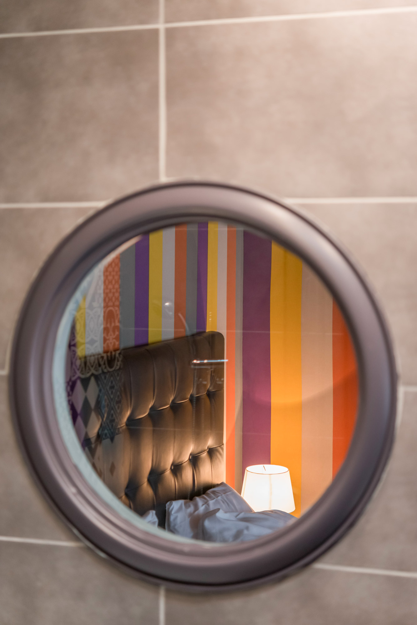 Gros plan sur un miroir de salle de bain reflétant le détail d'un lit avec une tête de lit en cuir