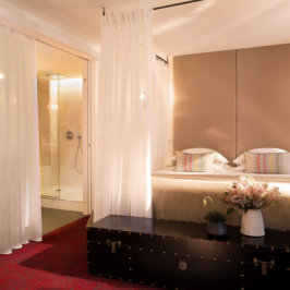 Spacieuse chambre à l'ambiance romantique avec coffre au pied du lit, baignoire et grand douche, lit king size