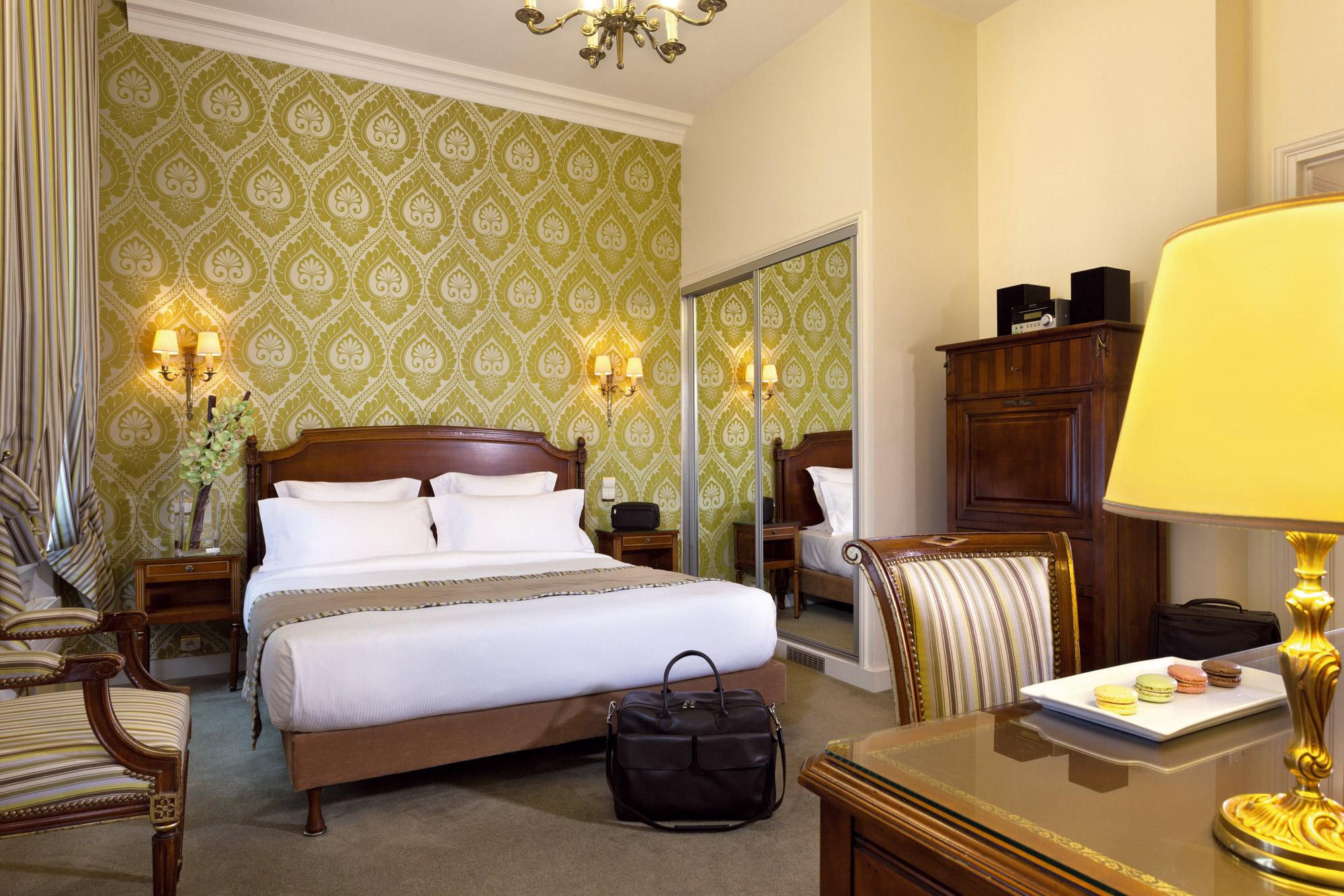 Chambre avec tapisserie aux murs de couleur verte , lit en bois massif, bureau et armoire en bois
