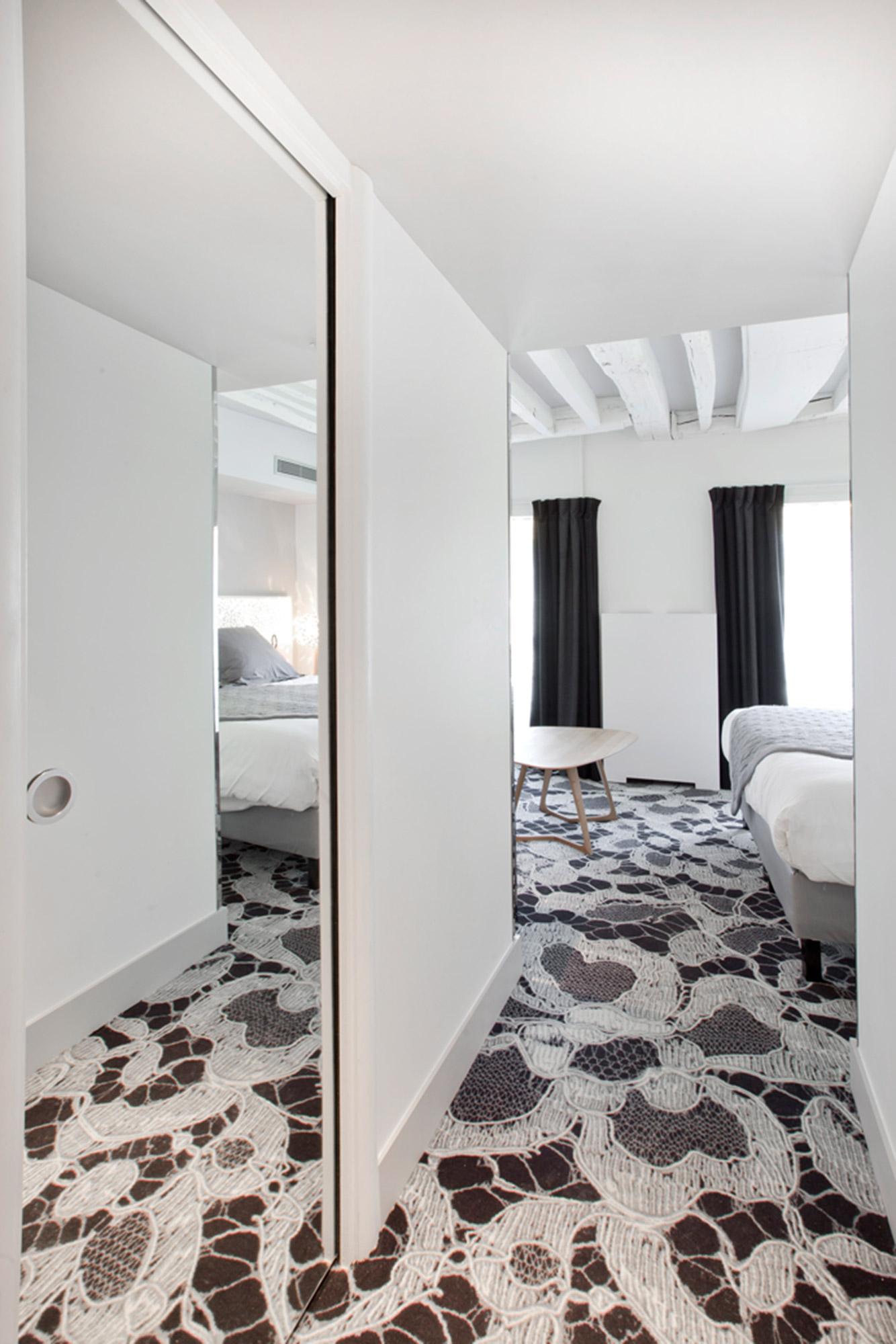 Placard avec miroir intégré reflétant un lit dans une chambre d'hôtel romantique avec au sol de la dentelle