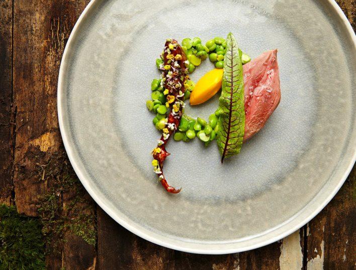 Plat de petit poid et canard dans une assiette plate ronde