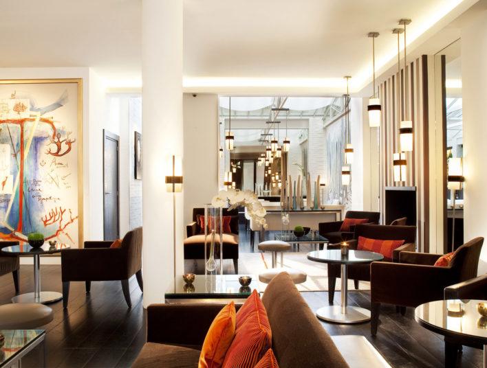 Grand salon avec fauteuils, tables basses, décoré de toiles moderne, baigné de lumière