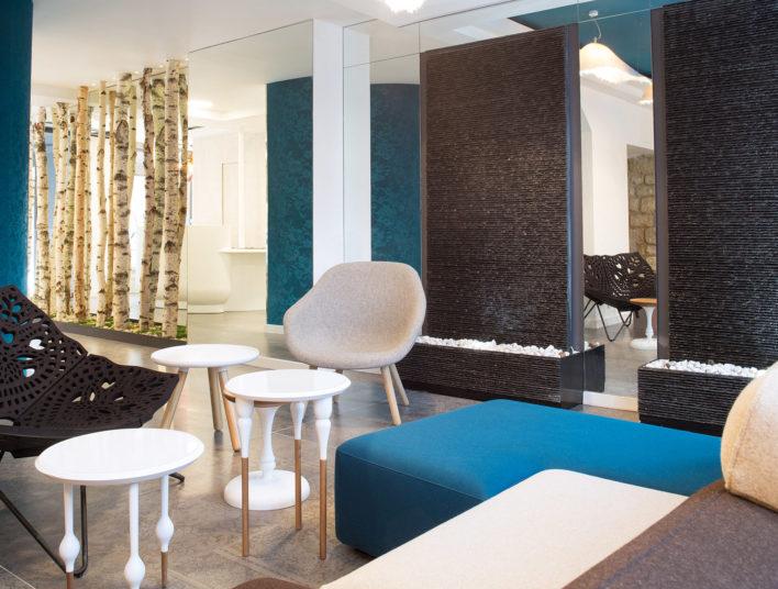 Fauteuils modernes installés dans le hall d'un hôtel avec troncs d'arbres détournés en séparateur d'espace