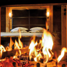 Gros plan sur un feu de cheminée au pied d'un lit double