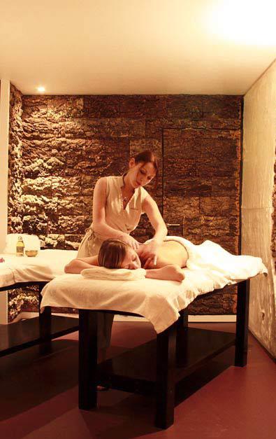 Une femme allongée sur une table de massage se fait masser par une masseuse professionelle