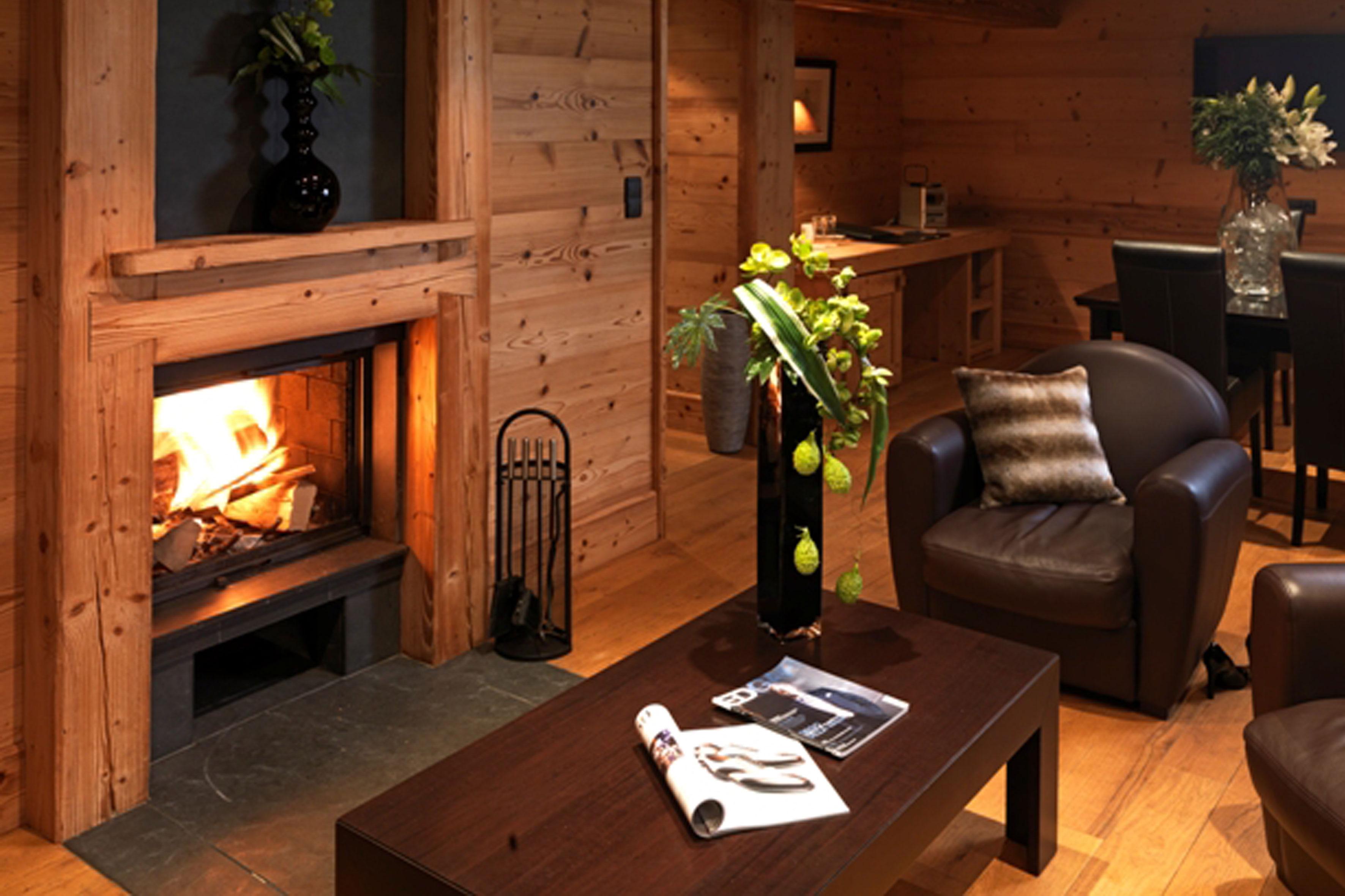 Feu de cheminée devant un espace salon avec table basse et fauteuil en cuir dans une ambiance chalet