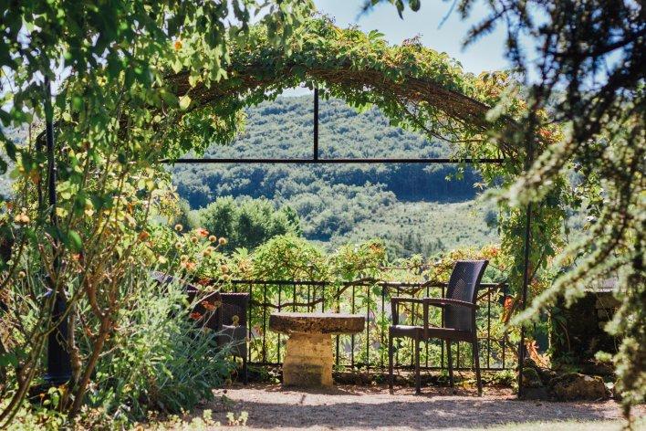 Terrasse ensoleillée avec vieille table basse en pierre et deux fauteils pour passer un moment intimiste avec vue sur la vallée
