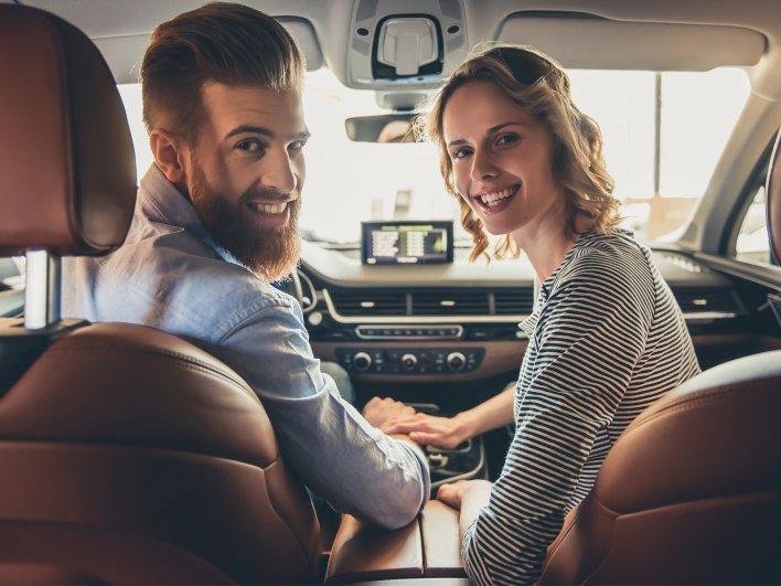 Jeune couple à l'intérieur d'une voiture se tenant la main comme des amoureux, prêts à partir en voyage
