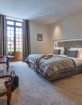 Grand lit dans une chambre pour deux personnes dans les tons beiges et gris