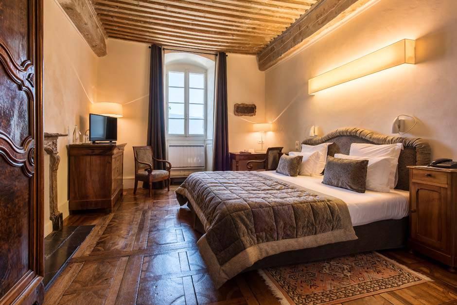 Lit double king size dans une chambre dans les tons beiges et gris, avec poutres apparentes au plafond