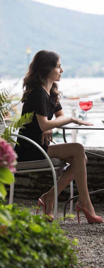 Femme assise à la table d'une terrasse donnant sur le Lac d'Annecy