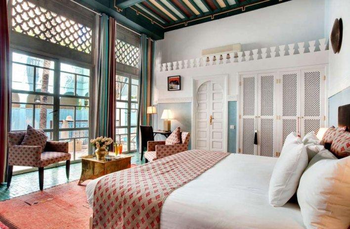 Chambre double avec lit king size dans les teintes ocres et bleu turquoise
