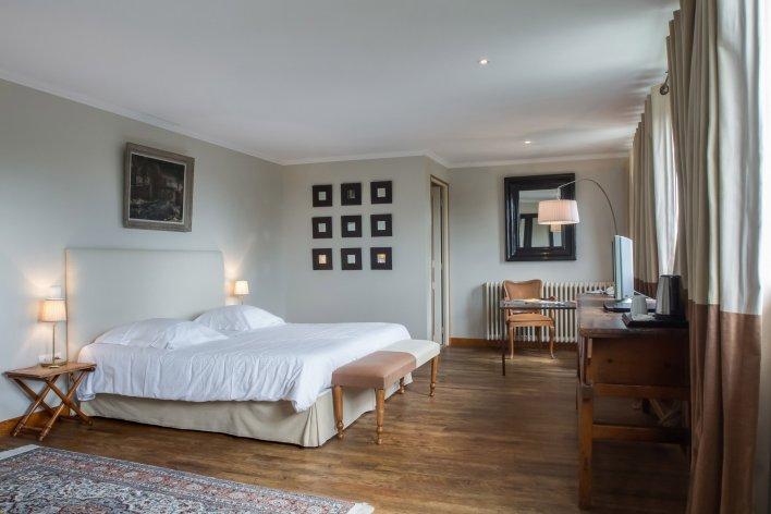 Chambre spacieuse avec parquet au sol, équipée d'un lit double, avec tableau et miroirs aux murs et disposant d'un bureau à l'ancienne