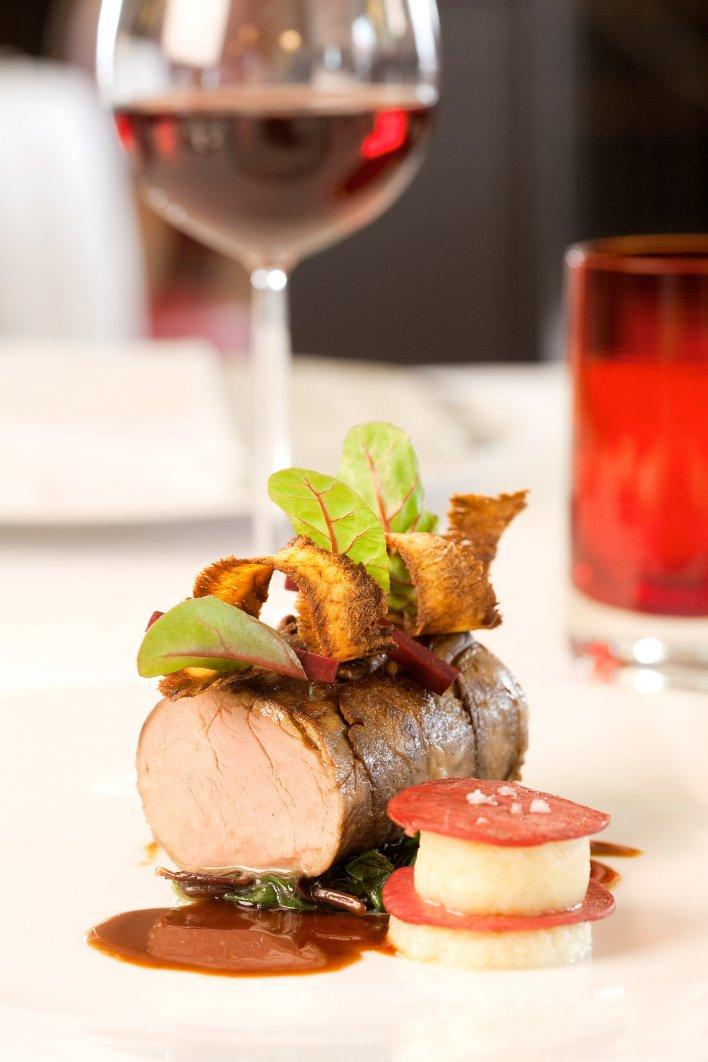 Plat de viande en sauce dressé sur table avec en arrière-plan un verre de vin rouge