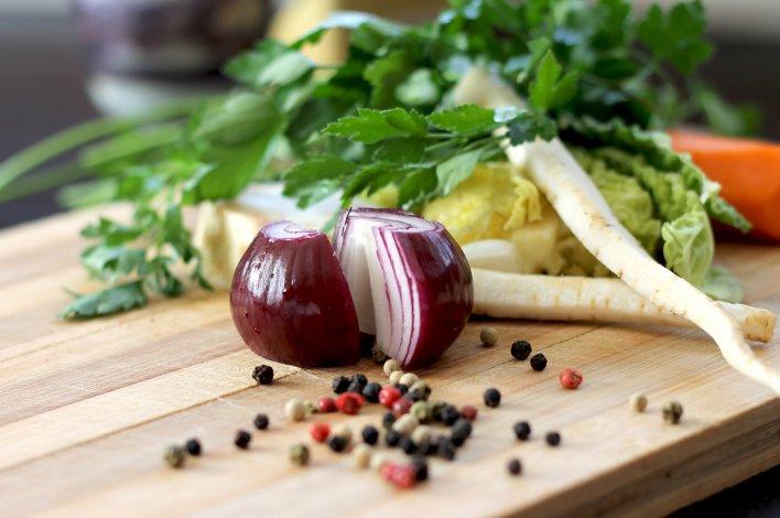 Oignon rouge coupé en deux, grains de poivre aux 5 baies parsemés, légumes de saison