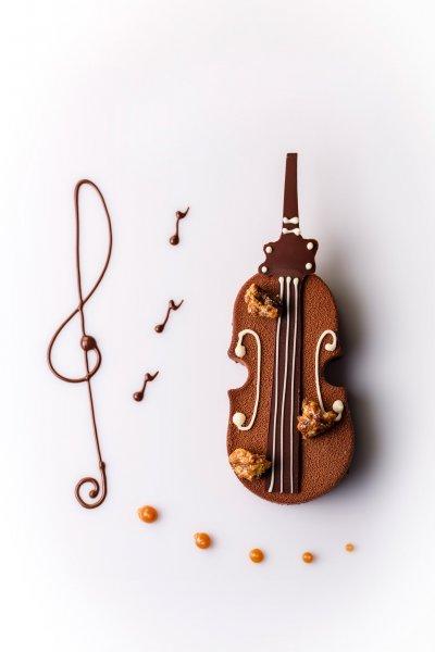 Clé de sol et croches réalisées en coulis de chocolat, avec un violon tout en chocolat