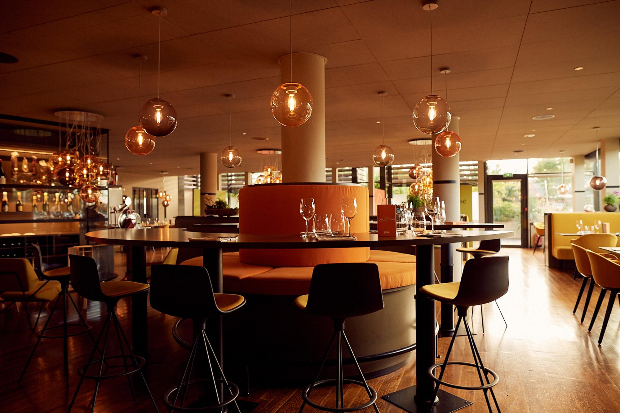 Salle de restaurant moderne dans les tons automnaux avec lustres en forme de boules de verre suspendues