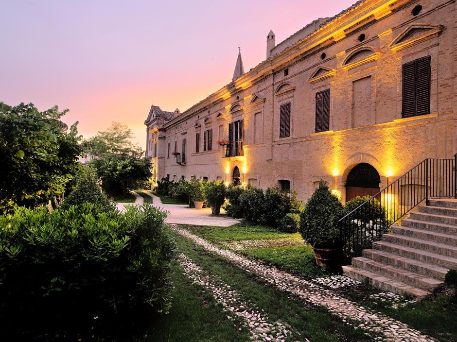 Façade du Castello Di Semivicoli, ciel rose, jardin avec arbustres