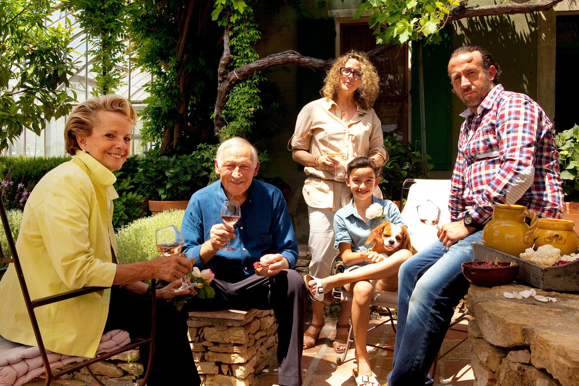 Photo de famille réalisée dans un jardin, réunissant 4 générations en train de déguster un vin rosé et un petit chien
