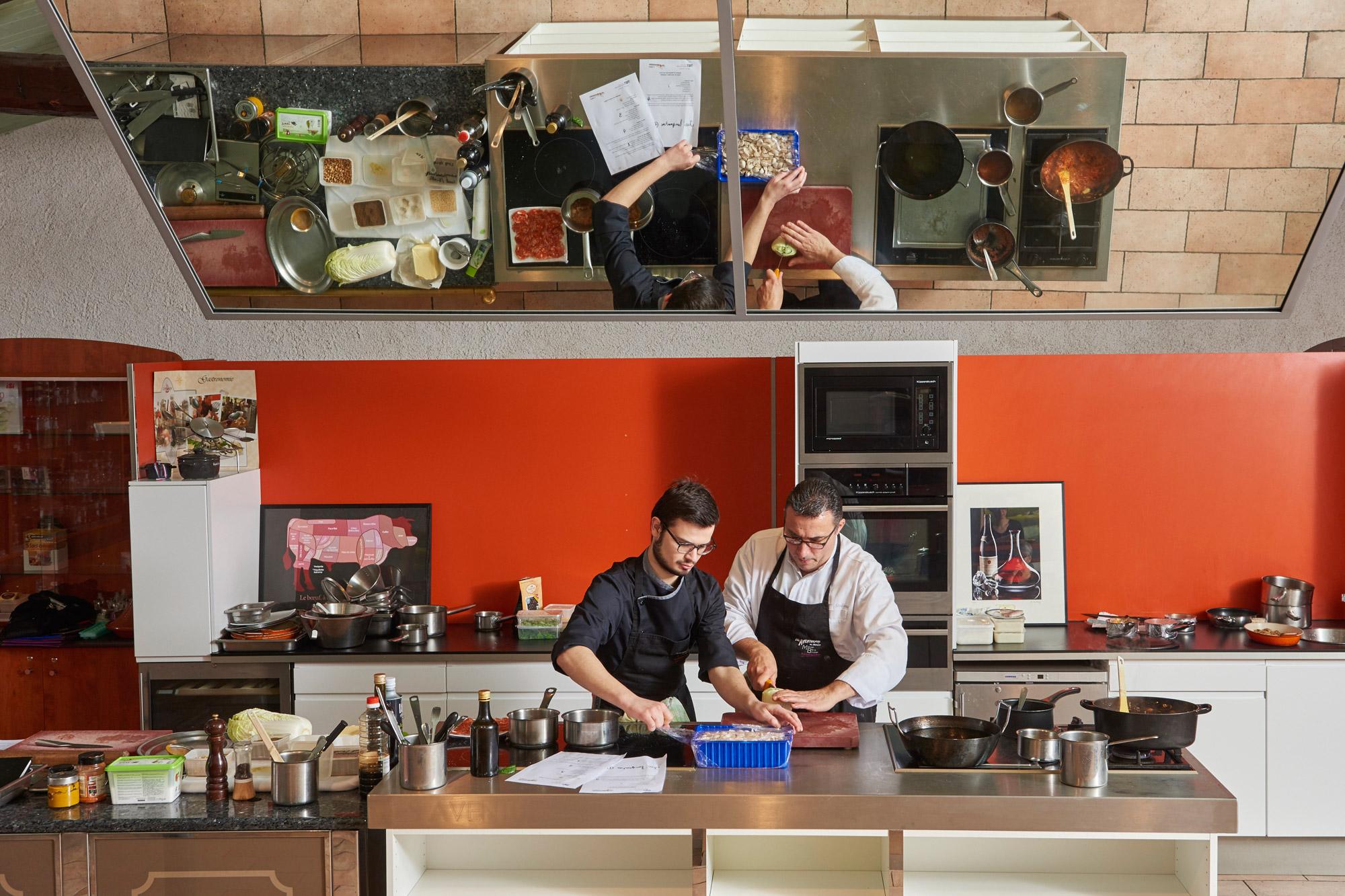Grande cuisine servant aux cours de cuisine, dans laquelle 2 chefs sont en train de réaliser une découpe de viande.