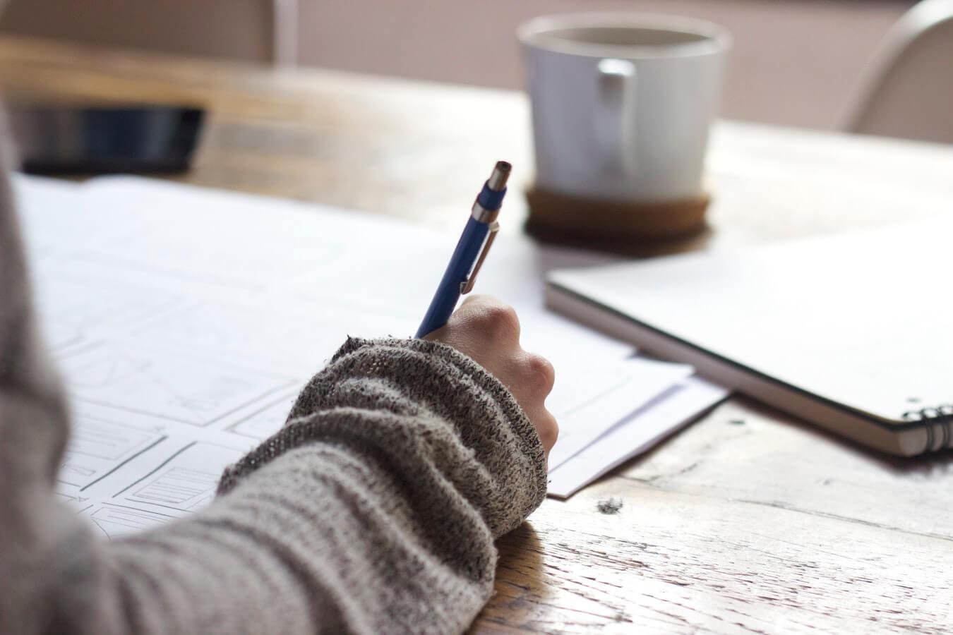 gros plan sur une main droite tenant un stylo bille sur une table en bois