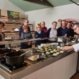 Groupe mixte de dix personnes en train d'assister à un cours de cuisine prodigué par le chef du Manoir de la Boulaie