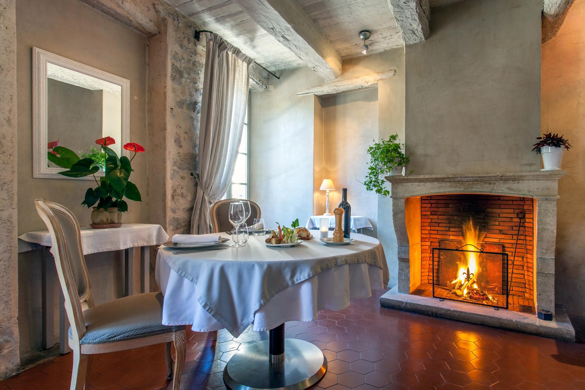 Table ronde dressée pour un couple d'amoureux dans une pièce avec poutres apparentes et feu de cheminée allumé