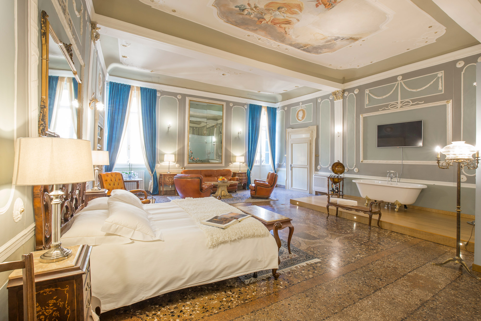 Chambre spacieuse avec baignoire type charleston face au lit sur estrade en bois, agrémentée d'une peinture italienne au plafond