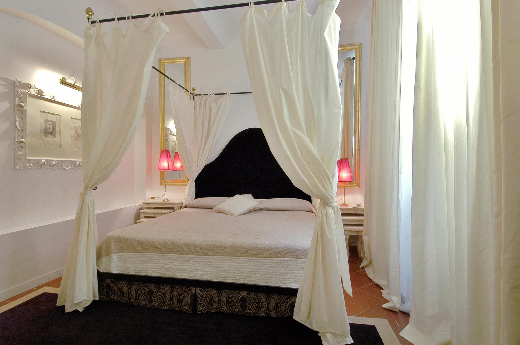 Grand lit avec baldaquins sur les 4 côtés, et tête de lit noire accompagnée de miroirs et lampes de chevets pour une ambiance romantique type Saint Valentin