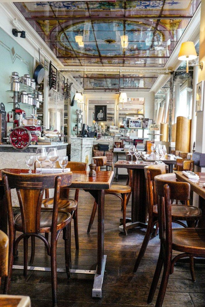 Salle de bistrot typiquement parisien avec plafond miroir décoré