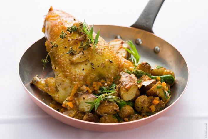 Plat de poulet typique de bistrot, servit dans une poêle en cuivre
