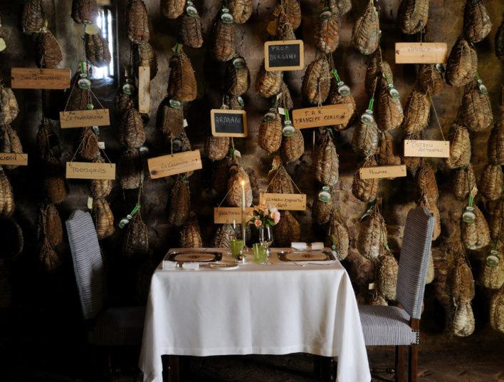 Table dressée pour deux couverts face à un mur de jambons typiques de l'Itale