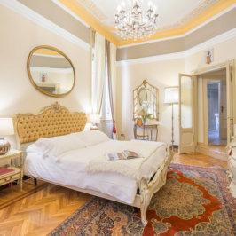 Chambre spacieuse décorée à l'italienne avec tête de lite capitonnée, miroirs, parquet