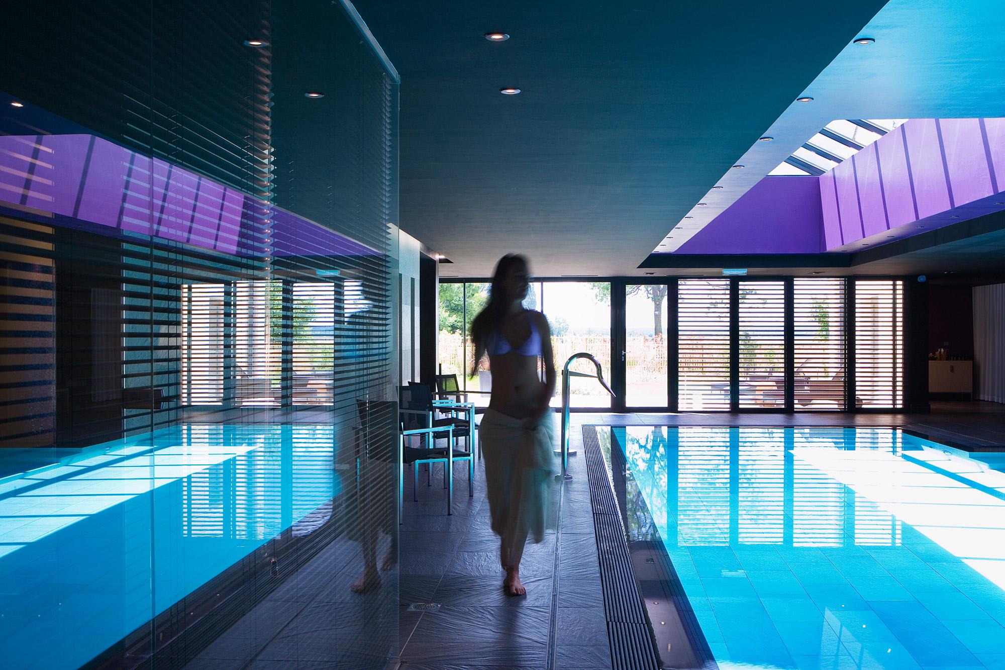 Salle spa design avec jeune femme marchant au bord de la piscine