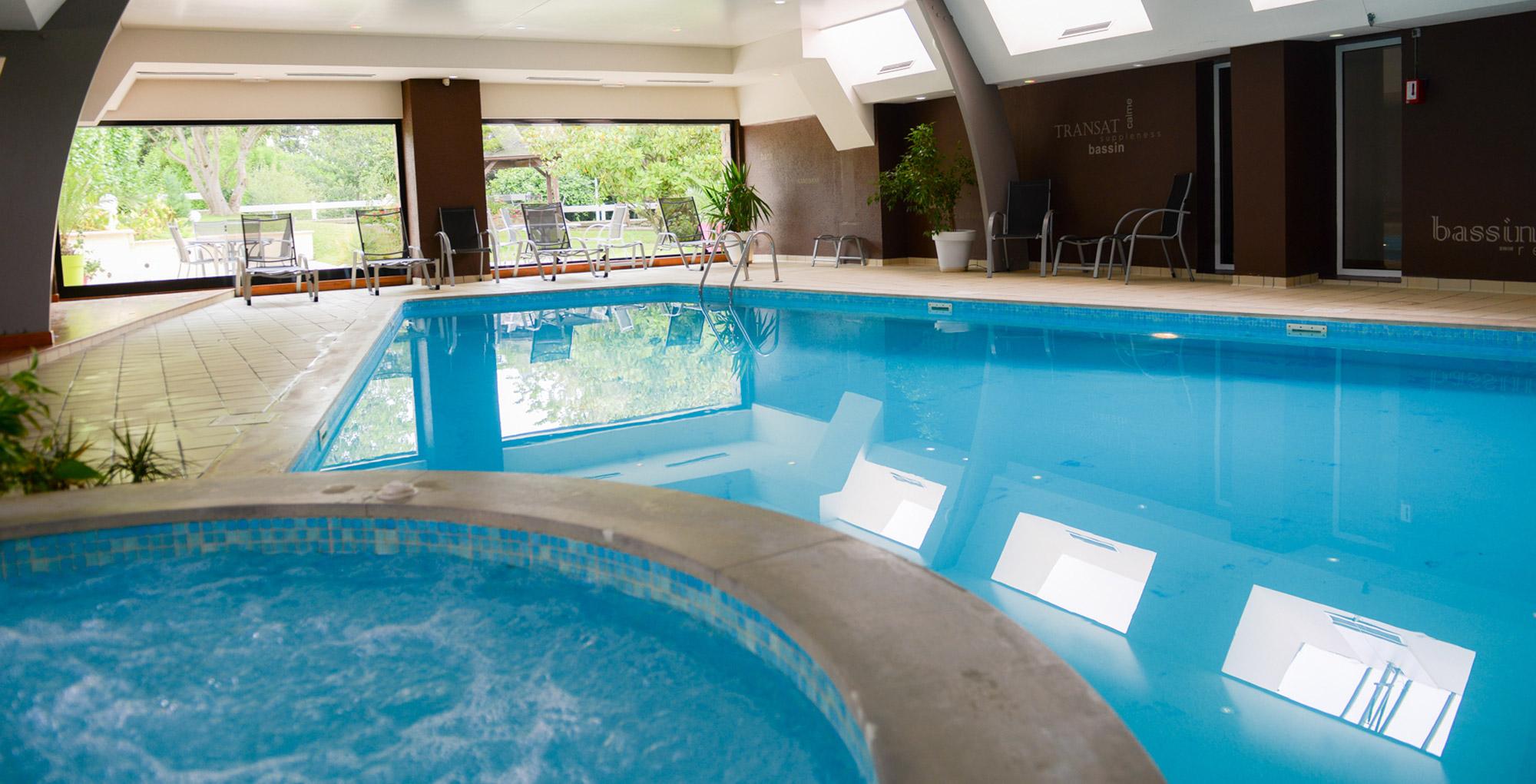 Spa à remous et piscine intérieure avec vue sur jardin paysager