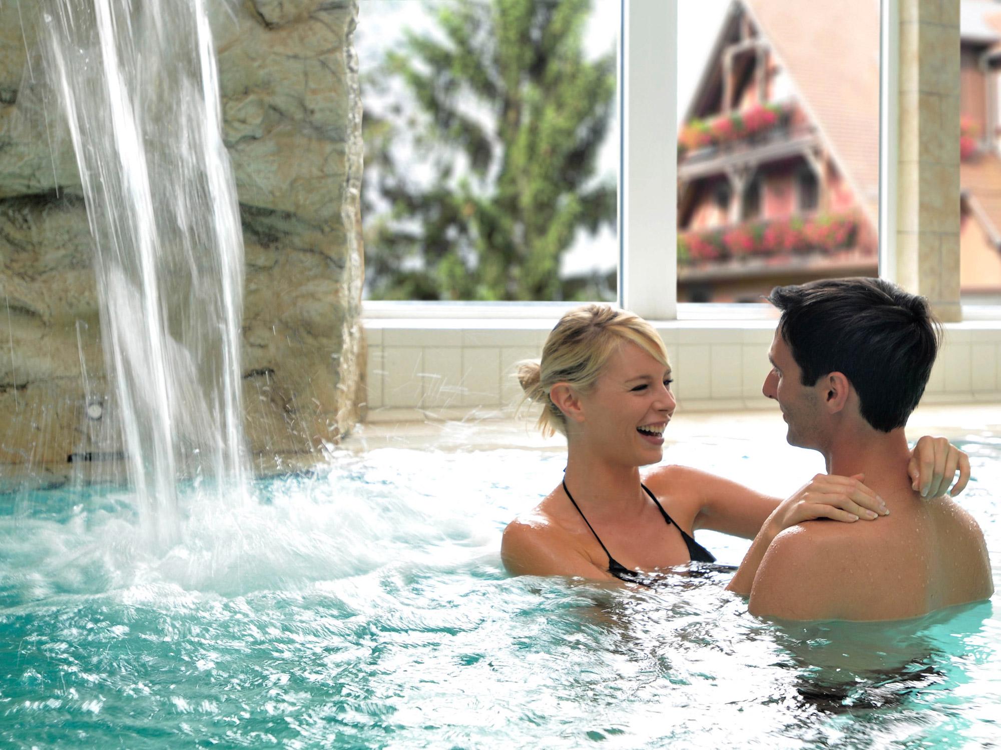 Jeune couple immergé dans l'eau d'une piscine en train de se détendre