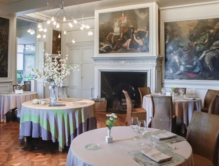 Salle de restaurant esprit château, avec des toiles de peintures aux murs représentant des scènes de bataille à cheval
