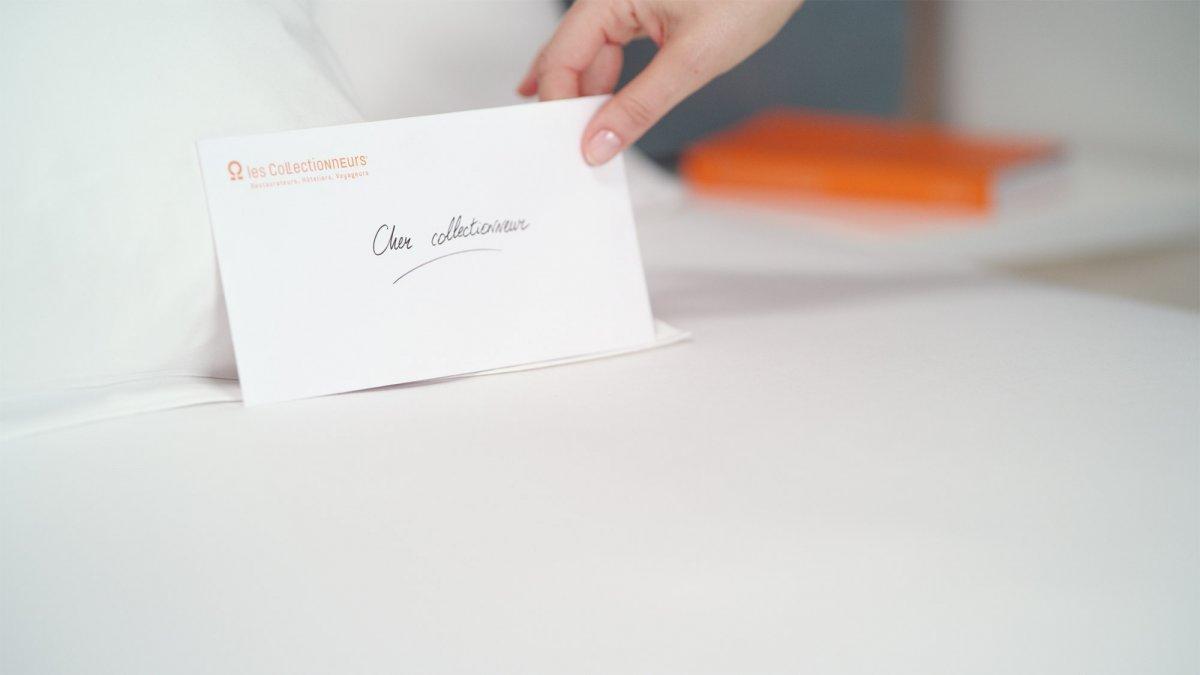 Carte posée sur l'oreiller d'un lit d'hôtel avec écrit dessus Cher collectionneur