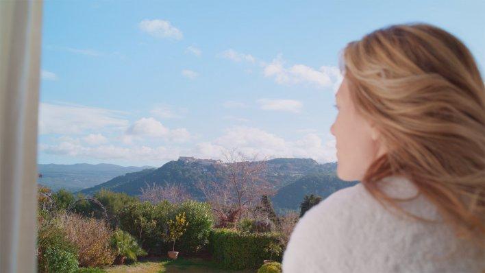 Jeune femme trentenaire en train de regarder un paysage de montagne depuis la fenêtre