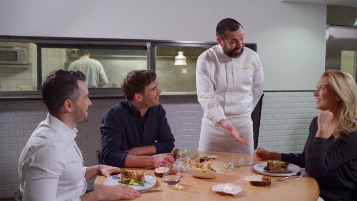 Trois trentenaires en train de dîner entre amis et discutant avec le chef à leur table