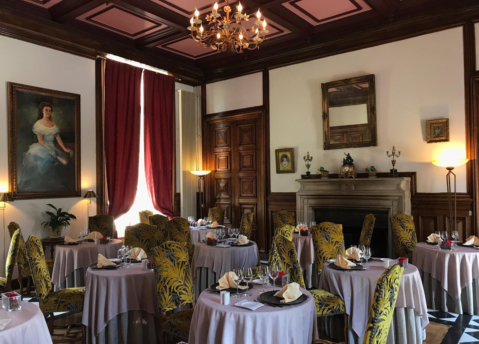 Salle de restauration dans bâtiment d'éqpoque avec ancienne cheminée, toiles peintes aux murs, chaises recouvertes de toile de velours