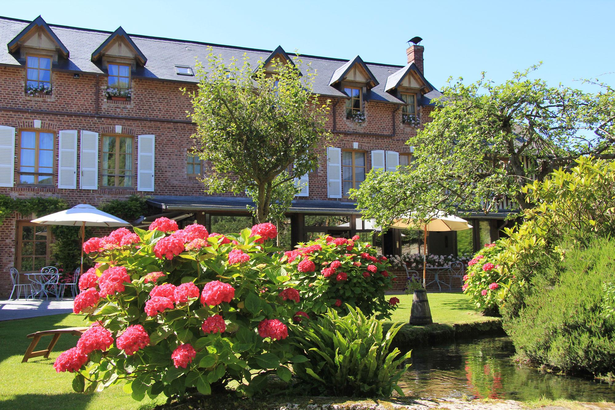 terrasse ensoleillée, bâtisse en pierres rouges apparentes et jardin fleuri